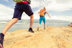 Corredores dos pares que correm com as trouxas na fuga do rocku no beira-mar fotos de stock