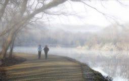 Corredores en niebla por el agua Imagenes de archivo