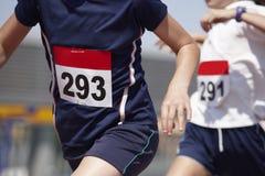 Corredores masculinos que concluyen una raza en una pista corriente Foto de archivo libre de regalías