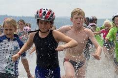 Corredores menores del triathlon en las series de Mudman del aQuelle foto de archivo libre de regalías
