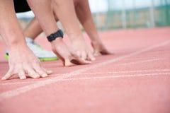 Corredores no início da pista de atletismo Imagens de Stock
