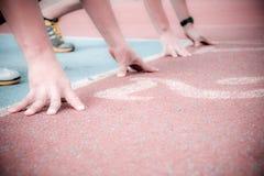 Corredores no início da pista de atletismo Fotos de Stock