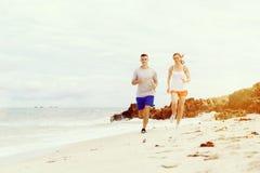 corredores Pares jovenes que corren en la playa Imagenes de archivo
