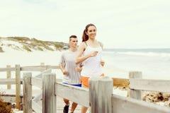 corredores Pares jovenes que corren en la playa Foto de archivo libre de regalías