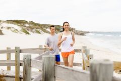 corredores Pares jovenes que corren en la playa Imagen de archivo