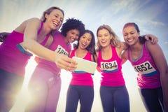 Corredores que apoyan maratón del cáncer de pecho y que toman selfies Imagenes de archivo