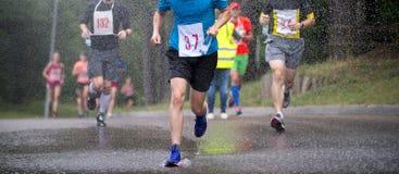 Corredores que corren bajo maratón de la ciudad de las gotas de lluvia imagenes de archivo