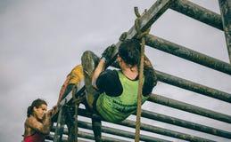 Corredores que escalam a estrutura em um teste da raça de obstáculo extrema imagens de stock royalty free