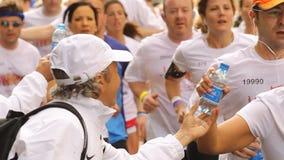 Corredores que toman la botella de agua
