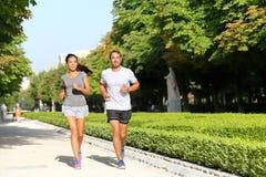 Corredores running dos pares que movimentam-se no parque da cidade Fotografia de Stock