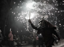 Correfoc 033. A man dressed as a devil runs while holding a fire stick over a cheering crowd during a Correfoc celebration festivity in the island of Mallorca Royalty Free Stock Photos