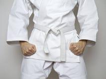 A correia branca do lutador ereto centrou o terno do branco das artes marciais Foto de Stock Royalty Free