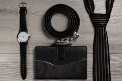 Correia de couro de Dlack, relógio, laço de seda, caderno em um backgrou cinzento Foto de Stock