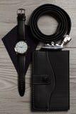Correia de couro, relógio, lenço de seda, caderno em um woode cinzento Imagens de Stock Royalty Free