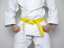 A correia ereta do amarelo do lutador centrou o terno do branco das artes marciais Imagem de Stock