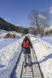 A correia transportadora de ascensão ao novatos corre para crianças e pais na estância de esqui com as montanhas no fundo Imagem de Stock