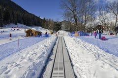 A correia transportadora de ascensão ao novatos corre para crianças e pais na estância de esqui com as montanhas no fundo Foto de Stock