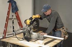 A correia vestindo da ferramenta do carpinteiro masculino e o corte da placa de madeira com costeleta profissional viram na casa  fotos de stock royalty free