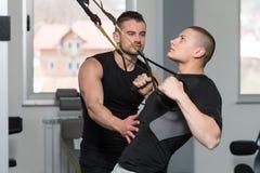 Correias da aptidão de Helping Man On Trx do treinador do Gym Imagens de Stock