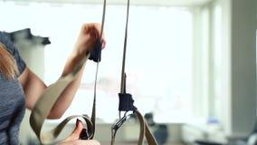 Correias TRX da aptidão Jovem mulher antes de treinar no gym video estoque