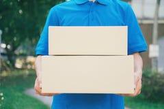 Correio do servi?o de entrega que est? na frente da casa com caixas fotos de stock