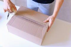 Correio Manstanding na estação de correios, caixa de Brown da fita da colagem em todo o S Imagens de Stock