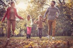 Correndo con la mamma ed il papà è divertimento, bambine con i genitori a Immagine Stock Libera da Diritti