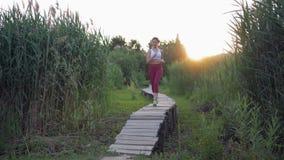 Correndo na natureza, mulher ativa dos esportes com corpo bonito em movimentar-se contratado roupa da aptidão na ponte de madeira video estoque