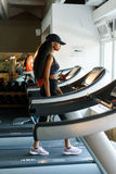 Correndo sulla pedana mobile in palestra o sul club di forma fisica - donna di colore che si esercita per guadagnare adattat Fotografia Stock Libera da Diritti