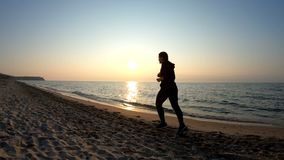 Correndo sulla spiaggia sabbiosa al tramonto video d archivio