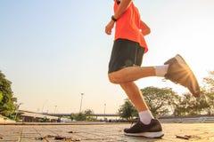 Correndo sulla strada con luce solare/corridore dell'uomo Fotografia Stock Libera da Diritti