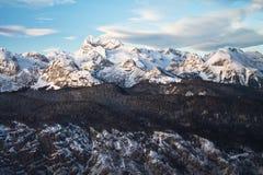 Corrente alpina bonita de montanhas nevado de cumes julianos no céu azul do por do sol Fotografia de Stock Royalty Free