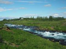 Corrente blu del fiume del ghiacciaio in un'erba verde immagine stock