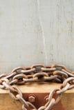 A corrente de aço oxidada rolou acima com fundo de madeira branco Fotos de Stock
