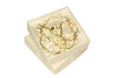 Corrente de prata com as pérolas & o anel no macro branco da caixa de presente isolados Fotografia de Stock Royalty Free