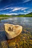 Corrente del fiume della montagna di acqua nelle rocce con cielo blu Fotografie Stock Libere da Diritti