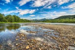 Corrente del fiume della montagna di acqua nelle rocce con la s blu maestosa fotografia stock libera da diritti