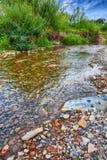 Corrente del fiume della montagna di acqua nelle rocce con la s blu maestosa immagine stock libera da diritti