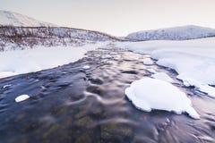 Corrente dell'acqua con le rocce in un paesaggio di inverno nella penombra Fotografie Stock Libere da Diritti