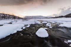 Corrente dell'acqua con le rocce in un paesaggio di inverno nella penombra Immagini Stock