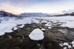 Corrente dell'acqua con le rocce in un paesaggio di inverno nella penombra Immagine Stock