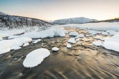 Corrente dell'acqua con le rocce in un paesaggio di inverno nella penombra Fotografie Stock