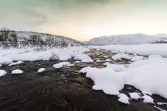 Corrente dell'acqua con le rocce in un paesaggio di inverno nella penombra Immagine Stock Libera da Diritti