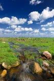 Corrente dell'acqua nel campo e nel cielo blu Immagini Stock Libere da Diritti