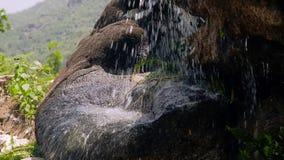 Corrente dell'acqua sulla cascata che circola sulle pietre vicino su Scorrimento dell'acqua del movimento lento del fiume della m stock footage