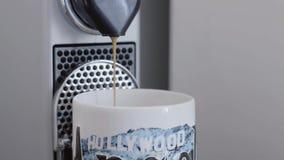 Corrente di versamento del caffè dal becco della macchina del caffè in tazza con la stampa di HOLLYWOOD stock footage