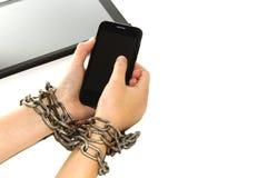 A corrente do ferro amarra junto as mãos e o smartphone - conceito do apego do telefone celular fotografia de stock royalty free