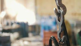 A corrente do metal balança na perspectiva dos soldadores na fábrica vídeos de arquivo