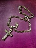 corrente do ouro com uma cruz dourada em um fundo violeta imagens de stock