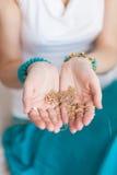 Corrente do ouro nas mãos de uma mulher oriental atrativa nova Fundo de borrão Fotos de Stock Royalty Free